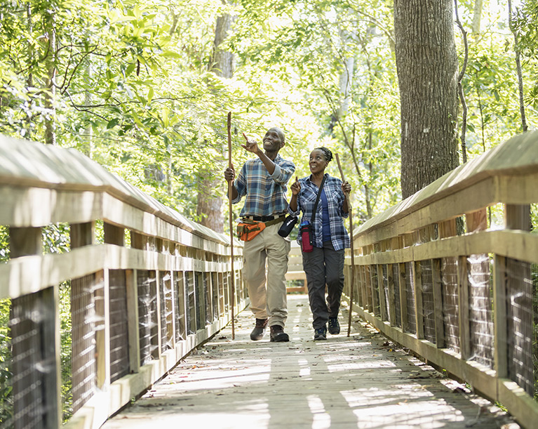 man and woman hiking on a nature trail with walking sticks