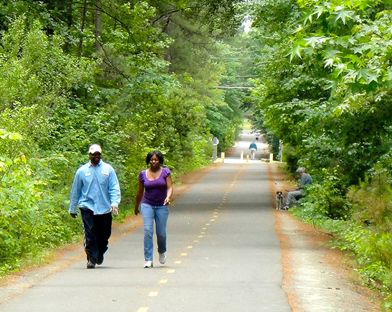 man and woman walking together on a greenway trail in nature
